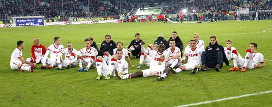 Mannschaft des 1.FC Köln nach Spiel auf dem Rasen sitzend