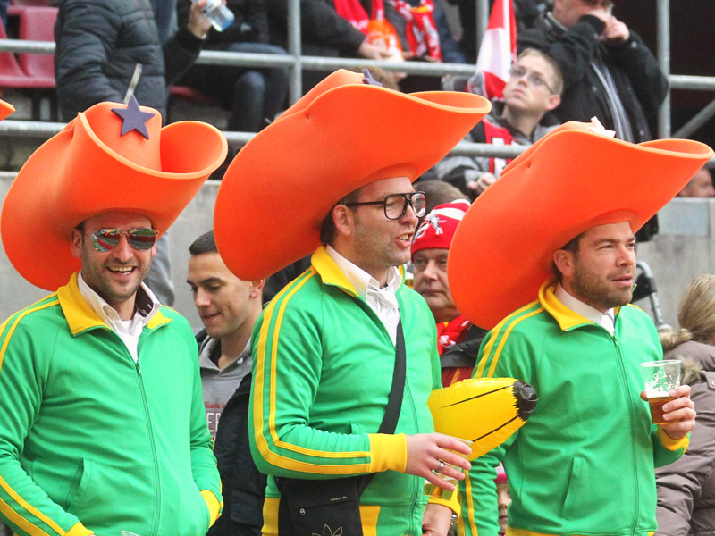 3 Fans des 1.FC Köln in grünen Trainingsjacken mit überdimensionierten orangen Hüten