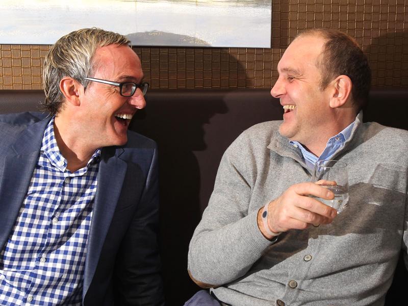 Alexander Wehrle und Jöreg Schmadtke vom 1.FC Köln sitzen auf einer Bank und lachen sich an