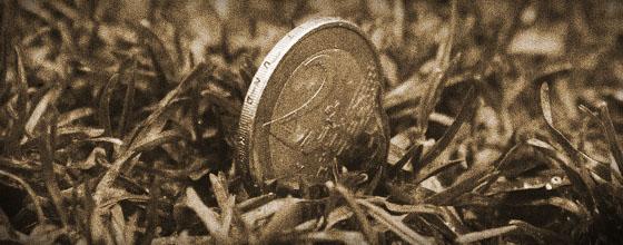 2€ Münze steckt senkrecht im Rasen