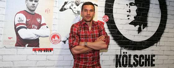 Lukas Podolski posiert vor der Wand seiner Lounge im RheinEnergieStadion