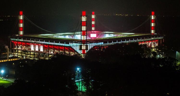 Rheinenergiestadion bei Nacht mit rot/weiß beleuchteten Pylonen